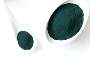 spoon of spirulina algae powder isolated on white background. Top view