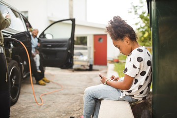 Side view of girl using smart phone while sitting in front yard