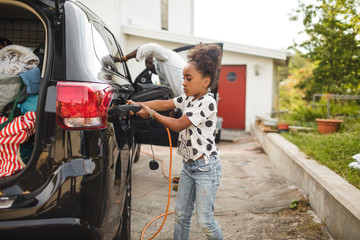 Girl connecting cable to electric car on driveway