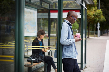Mid adult commuters waiting at bus stop in city