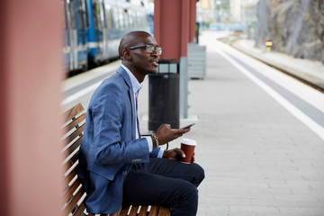 Thoughtful businessman sitting with smart phone and coffee at railroad station