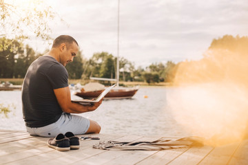 Mature man using laptop while sitting on jetty over lake during vacation