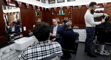 Britain's Prince William speaks to speaks to Dean Hamilton and Paul Richardson during a visit to Pall Mall Barbers in London