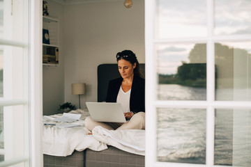 Woman using laptop while sitting on bed seen through doorway in holiday villa