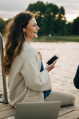 Smiling woman listening music on mobile phone while sitting at jetty