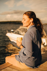 Smiling mature woman having coffee while using digital tablet at patio against lake during vacations