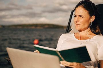 Thoughtful woman with laptop holding diary while looking away against lake