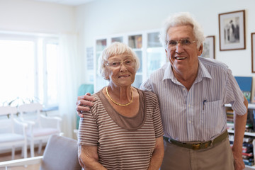 Portrait of senior couple standing arm around in nursing home