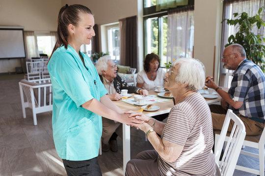 Nurse comforting senior woman while having breakfast at nursing home