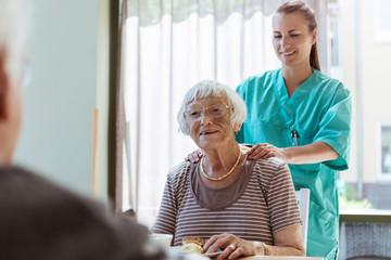 Smiling female caretaker massaging shoulders of senior woman at home