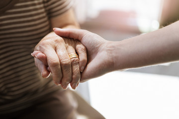 Close up of nurse holding hand of senior woman