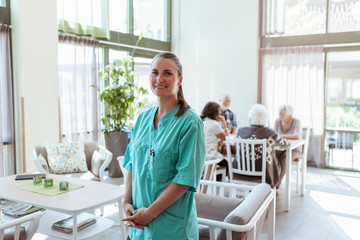 Portrait of smiling female healthcare worker with senior people in background at nursing home