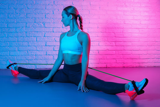 Tender young slim gymnast woman in sports clothing stretching with elastic band in front of brick wall in neon lights. Flexible muscular woman doing gymnastic split.