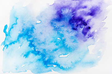 top view of blue and purple spills on white paper