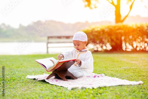 Little Muslim boy reading holy Quran on grass field near