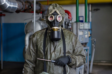 Man in chemical protection suit .with radiation dosimeter
