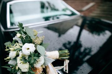 Beautiful white wedding bridal bouquet on the car