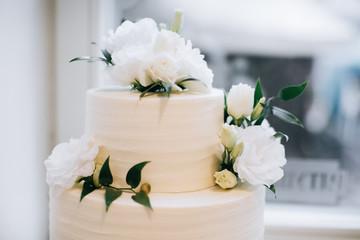 Beautiful and tasty white wedding cake at wedding reception with fresh flowers