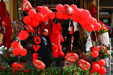 Man looks at a red teddy bear outside a shop selling Love signs, chocolate and flowers on Valentine's Day in Gaza City