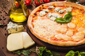 Classic Italian Four Cheese Pizza with Mozzarella, Brie, Dor Blue, Radamir on a dark wooden background with ingredients around (close)