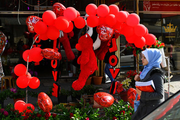 Woman walks past a red teddy bear outside a shop selling Love signs, chocolate and flowers on Valentine's Day in Gaza City