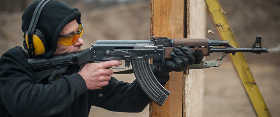 Combat riffle machine gun shooting from behind cover or barricade