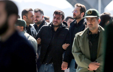 A relative of members of Iran's elite Revolutionary Guards, who were killed by a suicide car bomb, mourns at Isfahan airport