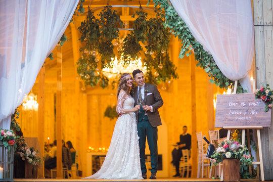 Beautiful fashion wedding couple posing in front of barn wedding venue