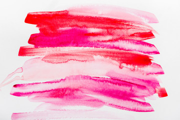 top view of pink and red brushstrokes on white paper