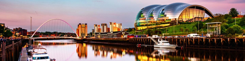 Famous Millennium bridge at sunset. Illuminated landmarks with river Tyne in Newcastle, UK