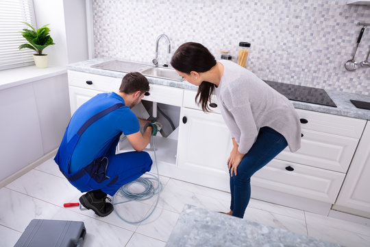 Male Plumber Cleaning Clogged Sink Pipe With Drained Cable