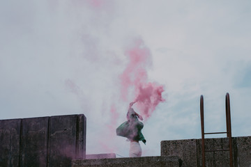 Young woman jumping on a rooftop with pink smoke bomb.