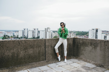 Beautiful woman fashion model posing on building rooftop.