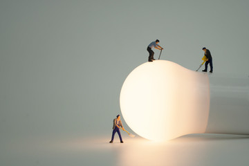 Miniature people with light bulb Wall mural