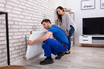 Repairman Installing Radiator On Brick Wall At Home