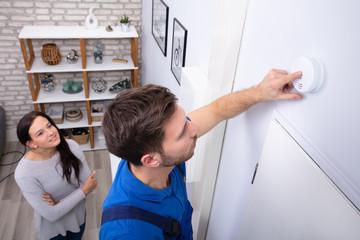 Repairman Installing Smoke Detector On Wall