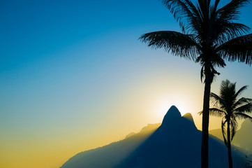 Scenic sunset view of Two Brothers Mountain backlit by the setting sun with palm tree silhouettes lining Ipanema Beach in Rio de Janeiro, Brazil