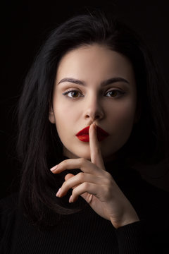 Hush be quiet woman isolated on black. Beautiful girl with finger on her lips.
