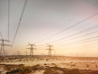 Electric towers in desert with dubai city in background