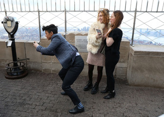 Guests watch as Helena Barquet and Fabiana Faria (unseen) pose for photos following their Valentine's Day wedding ceremony at the top of the Empire State Building in New York