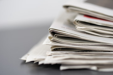 Macro shot of a stack of newspapers. The newspapers are folded