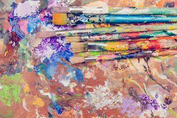 Set of paintbrushes on messy colorful wooden table, grungy background