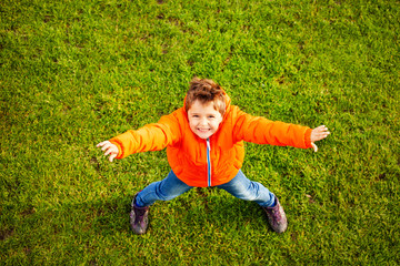 Boy standing on green grass with outstretched arms