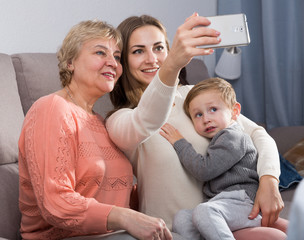 Two women and toddler are resting together and taking selfie