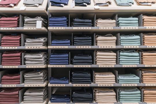 Various color shirts at shelf in shop