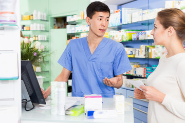 Korean man pharmacist is recommending medicine for young woman client near cashbox in apothecary.