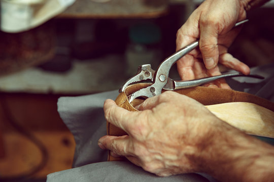Enjoying process of craft shoes creation. Workplace of shoe designer. Hands of shoemaker dealing with cobbler tool, close up