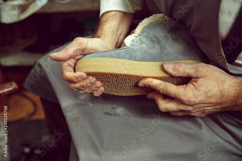 0108aef6b061 Enjoying process of creation custom made shoes. Workplace of shoe designer. Hands  of shoemaker dealing with cobbler tool