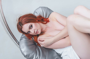 Beautiful naked woman lying with raised legs on a gray mattress hanging seat, white cloth. Women's health. sexuality.