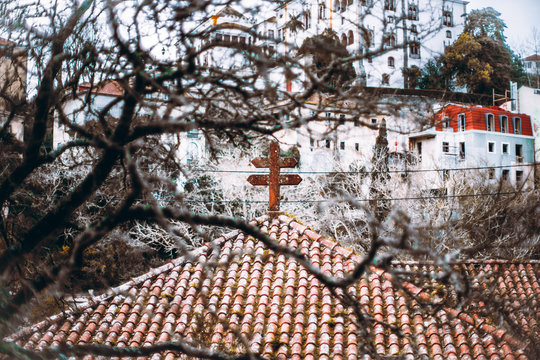 An antique weathered tiled roof with a stone Lorraine cross on it framed with multiple branches of the tree in a defocused foreground, a huge historical building on the hill in the background, Sintra